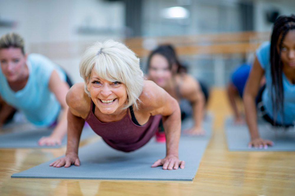 Senior Woman in Fitness Class in a Plank Pose Smiling