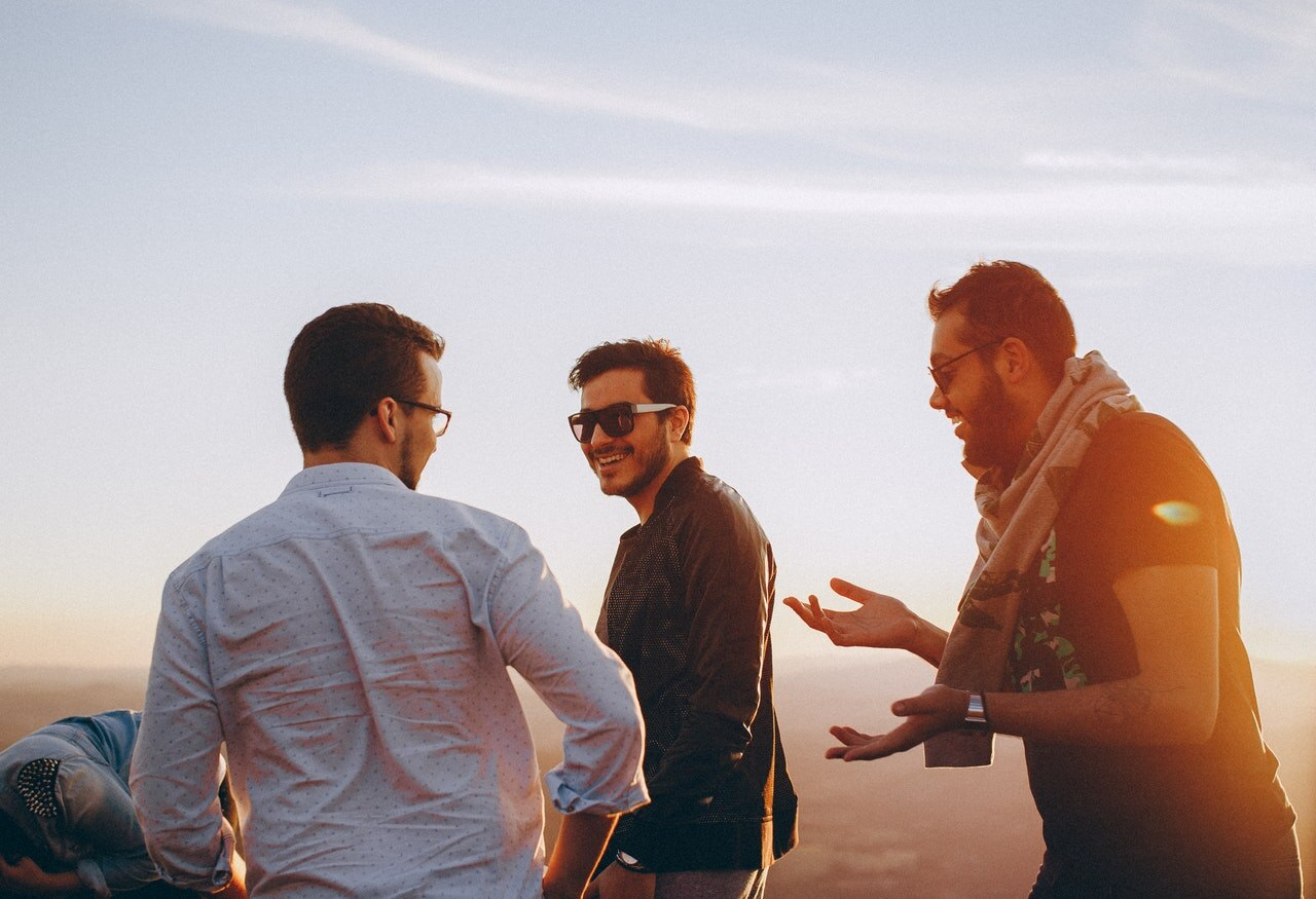Three men walk and talk outside, sunset behind them.
