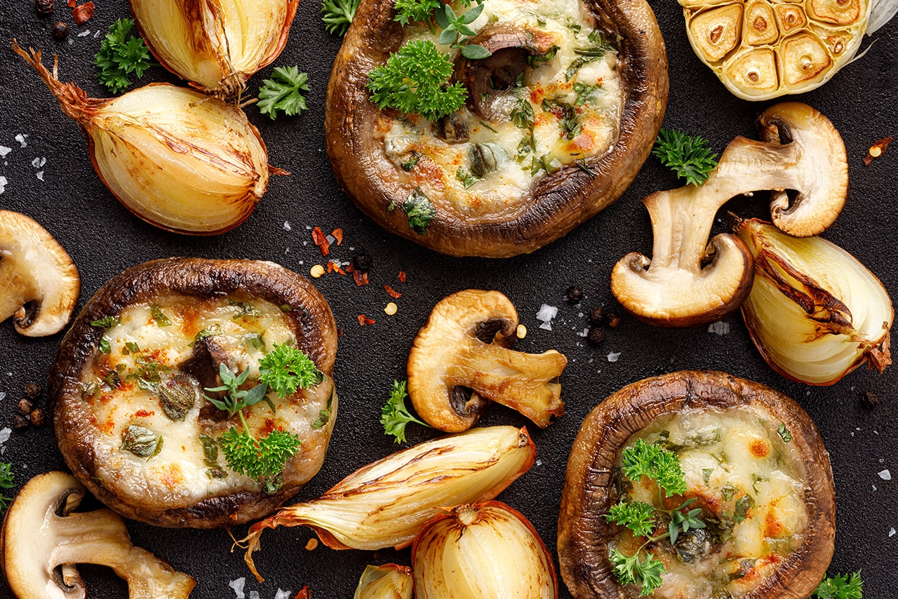 Mushrooms both stuffed and sliced laid out in a spread.
