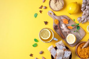 Ginger, turmeric, lemon, honey, and a variety of spices are strewn across a table, in bowls and on cutting boards.