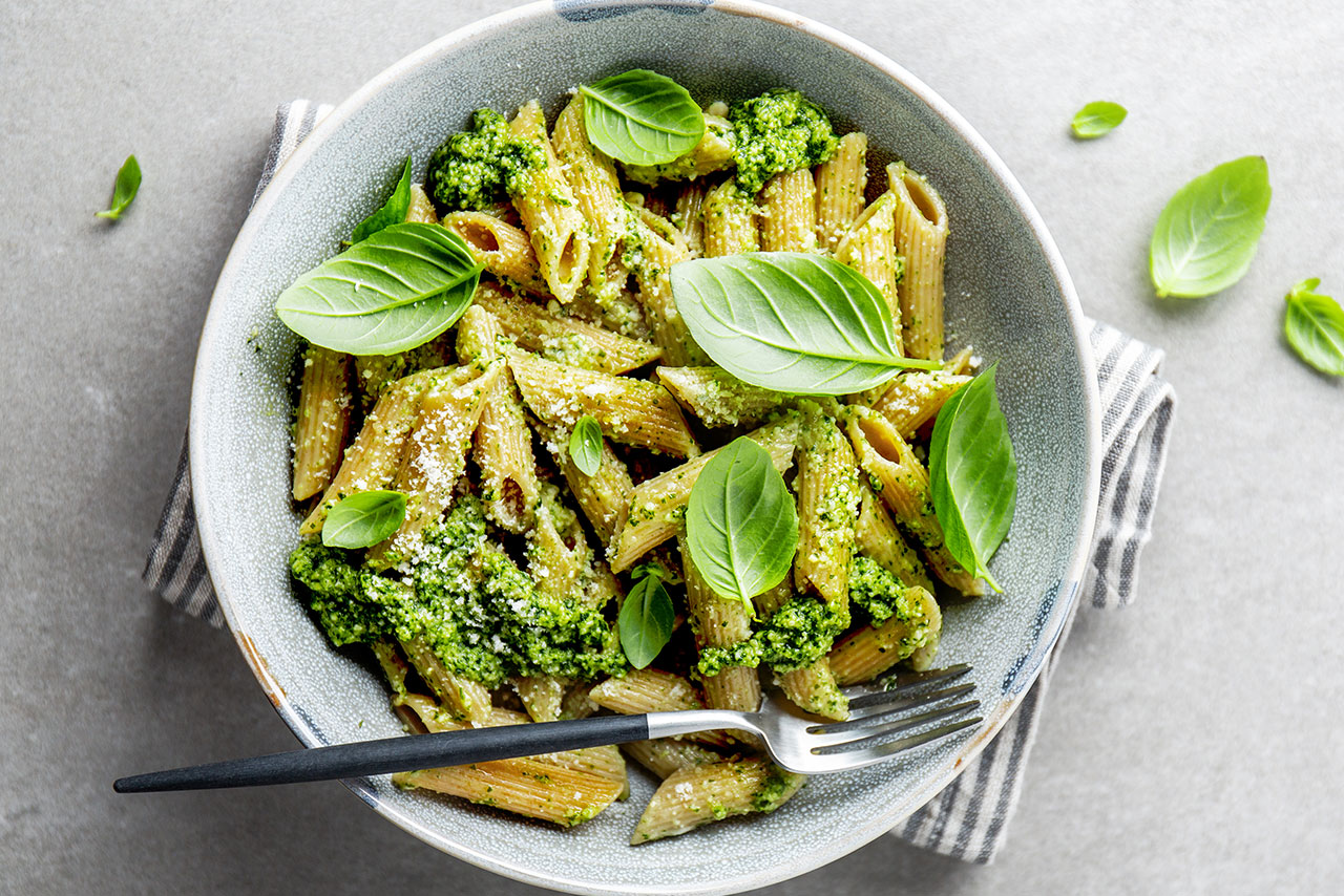 Penne with greens and gorgonzola prepared in bowl.