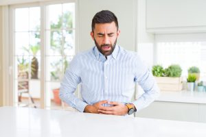 A man in a button-up shirt is closing his eyes and holding his stomach with both hands.