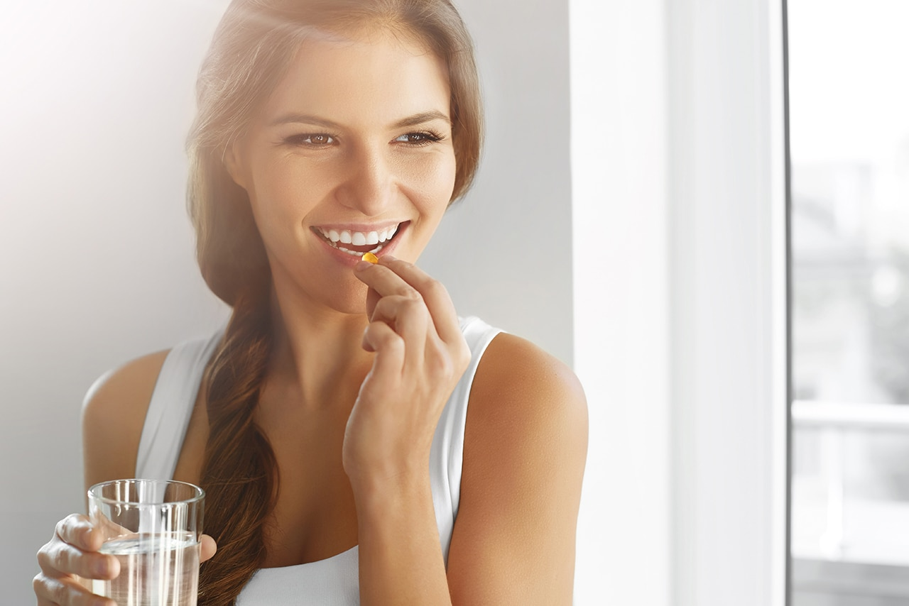 Woman takes a supplement, holding a glass of water.