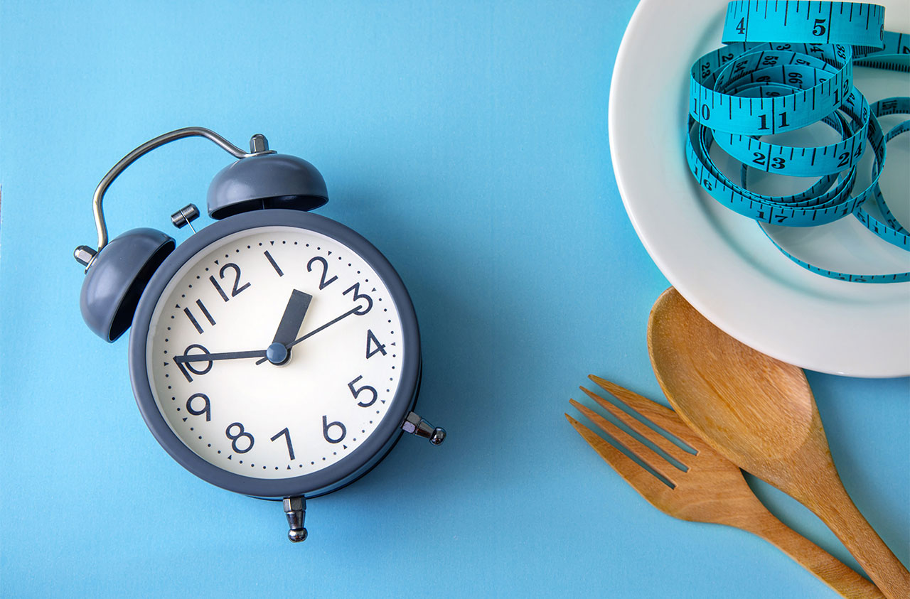 An alarm clock sits next to a plate with a blue measuring tape piled on top.
