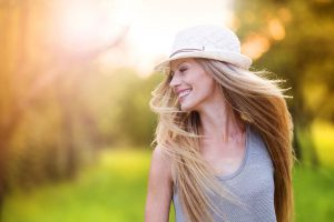 A woman wearing a hat is tossing her hair while walking in the sun.
