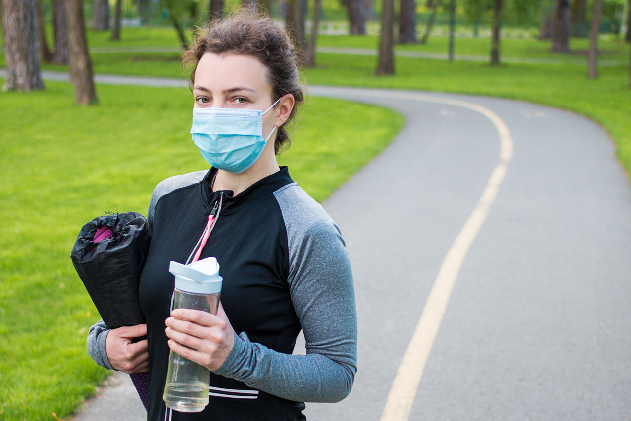 A woman in athletic apparel stands on a track wearing a face mask and holding a water bottle.