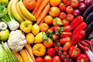 An assortment of produce is laid out in a rainbow color scheme.
