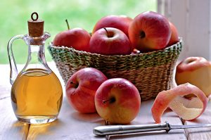 apples in a basket and vinegar in a bottle on a white table